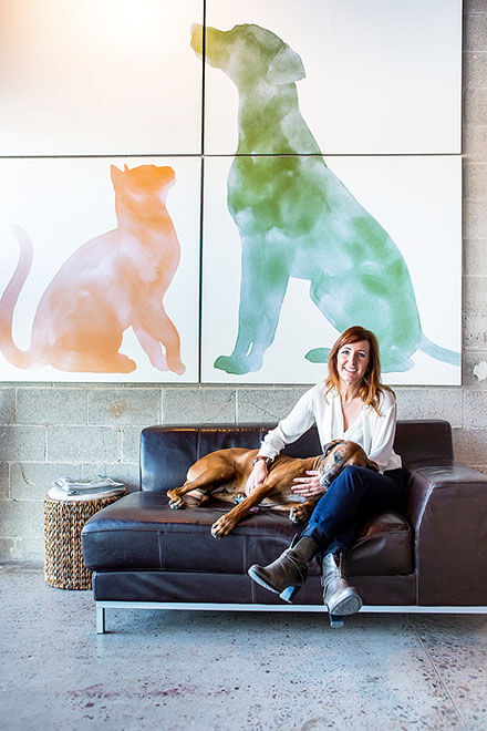 The Honest Kitchen founder Lucy Postins sitting with her dog in front of dog and cat art at her home office.